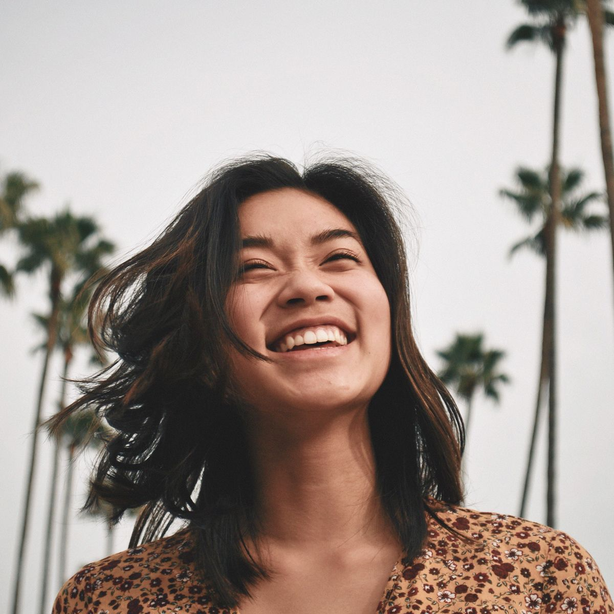 Woman smiling with palm trees in the background
